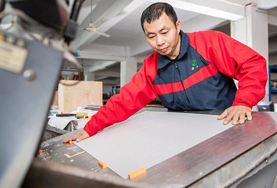 a-worker-using-the-die-cutting-machine